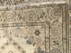 A Kashan rug with central lozenge medallion on a cream ground,