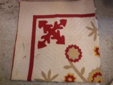 A vintage American quilt of red and crea