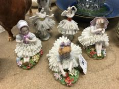 A collection of five Sitzendorf and other figures of young children in lace dresses,