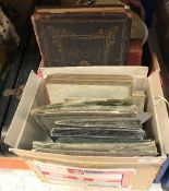 A box containing assorted Victorian and later postcards and photo albums to include postcards of