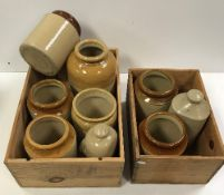 Two wooden wine crates containing various stoneware storage jars,