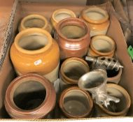 A box containing various stoneware storage jars and a box of assorted kitchenalia,
