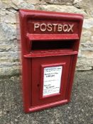 A modern reproduction metal red postbox,