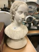 A painted plaster bust of a young girl,