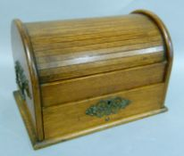 An Edwardian oak tambour top desk or smoker's compendium with compartments, pair of carrying handles