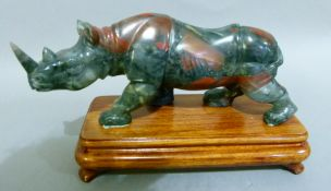 A soapstone carving of a rhinoceros, on mahogany stand 21cm wide x 12cm high