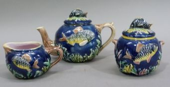A late 19th century majolica three piece tea service moulded with fish and coral on a blue ground,