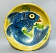 A studio pottery plate decorated with a blue fish on a mustard ground, 27cm diameter