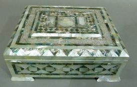 A mother of pearl casket the hinged lid centered with a raised tablet and a domed building in low