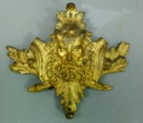 A gilt metal furniture mount cast as Pan, bearded and horned face mask within acorn and oak leaf