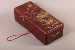 A Japanese red lacquer box and cover of rounded rectangular form, the pull off lid decorated in