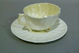 A Belleek nautilus cup and saucer, the shell shaped cup resting on a moulded circular saucer, saucer