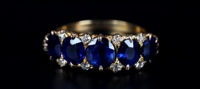A VICTORIAN SAPPHIRE AND DIAMOND RING in 18ct gold the five oval faceted sapphire claw set inline