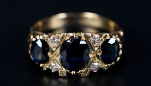 A SAPPHIRE AND DIAMOND RING the three graduated oval faceted sapphire claw set inline and