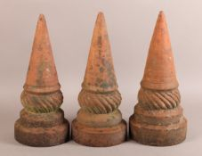 A SET OF THREE 19TH CENTURY TERRACOTTA FINIALS of conical and writhen form on circular plinth