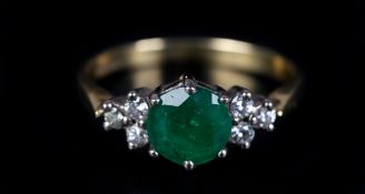 AN EMERALD AND DIAMOND RING in 18ct yellow and white gold, claw set to the centre with a circular
