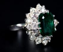AN EMERALD AND DIAMOND CLUSTER RING claw set to the centre with a step cut diamond within an