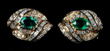 A PAIR OF EMERALD AND DIAMOND EARRINGS each claw set to the centre with an oval faceted emerald