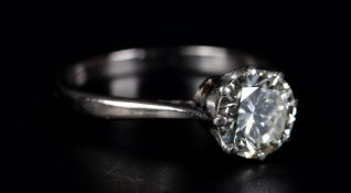 A SINGLE STONE DIAMOND RING in platinum the brilliant cut stone claw set flanked by tubed shoulders,