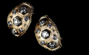 A PAIR OF DIAMOND EARRINGS the graduated brilliant cut stones collet set and raised above a