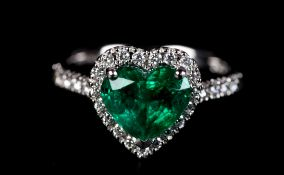 AN EMERALD AND DIAMOND CLUSTER RING in platinum the heart shaped faceted emerald claw set, raised
