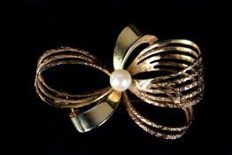 A CULTURED PEARL BOW BROOCH in 9ct gold, the 5mm set to the centre of a plain and textured ribbon