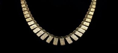 A FRINGE NECKLACE in 18ct gold c.1970 with textured graduated brick type links, approximate length