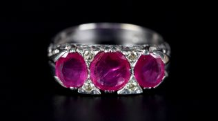 A RUBY AND DIAMOND RING in 18ct white gold the three graduated oval faceted rubies claw set inline