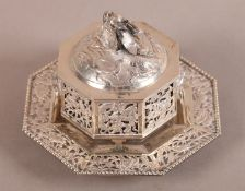 A CHINESE WHITE METAL TWO HANDLED BOX, COVER AND STAND, of octagonal form with pierced decoration