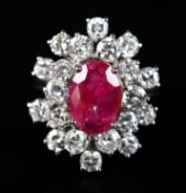 A RUBY AND DIAMOND CLUSTER RING claw set to the centre with an oval faceted ruby raised against a