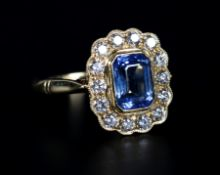 A SAPPHIRE AND DIAMOND CLUSTER RING in 18ct gold, the step cut sapphire collet set within a surround