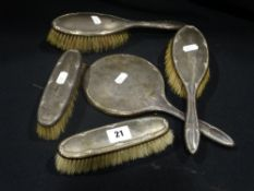 A Silver Backed Dressing Mirror With Four Silver Backed Brushes