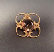 SMOKY QUARTZ SET NINE CARAT GOLD BROOCH the central oval cut quartz in quatrefoil setting, 2.7cm