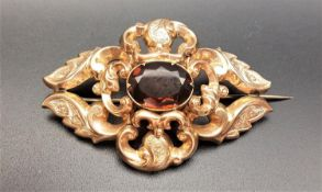 VICTORIAN QUARTZ SET BROOCH the pierced scroll decorated unmarked gold brooch with central oval