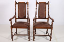 A PAIR OF CIRCA 1950s OAK ELBOW CHAIRS each with upholstered panelled back and seat with spiral