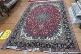 A TABRIZ WOOL RUG the wine ground with central panel filled with stylized flowerheads foliage and