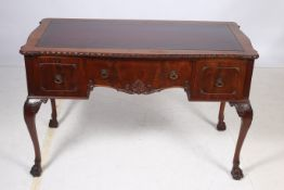 A CHIPPENDALE DESIGN MAHOGANY DESK of serpentine outline the shaped top with gadrooned rim and