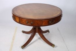 A 19TH CENTURY MAHOGANY AND ROSEWOOD CROSS BANDED DRUM TABLE the circular top with tooled leather
