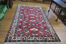 A PERSIAN HANDMADE WOOL RUG the wine ground with central panel filled with flowerheads serrated