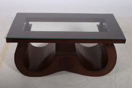 A CIRCA 1950s OAK COFFEE TABLE of rectangular outline with glazed top raised on a U shaped support