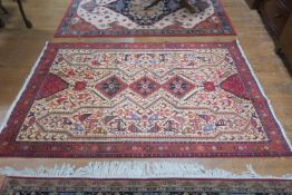 A PERSIAN HANDMADE WOOL RUG the beige ground with central panel filled with stylized animals