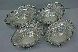 Set of four Edwardian pierced silver bonbon dishes of oval form with cherub mask decoration.