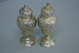 Pair of Victorian chased silver pepper pots with floral decoration (cased). London 1889. 3 ozt.