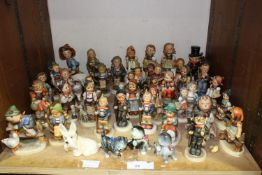 SECTION 29. Over 40 Goebel Hummel figures mainly of children, three cats and a dog with fly on his