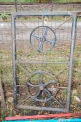 """A Metal gate decorated with a steering wheel and wheel 47 1/2"""" high x 32"""" wide."""