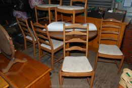 """A set of six """"Ercol"""" ladder-back Ash wood framed Dining Chairs and a matching oval Dining Table"""