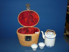 A wicker carrying basket with metal handles containing oriental Teapot and two cups.