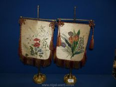 Two Victorian brass and fabric face Screens painted with flowers, with fringing and tassels,
