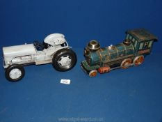 A vintage tin plate battery operated train and grey metal toy tractor.