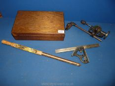 A vintage ground thermometer, wrought iron tower drill and set square in wooden box.